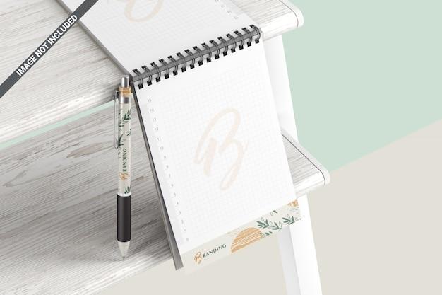 モックアップをブランディングする木製の棚にペンとノート