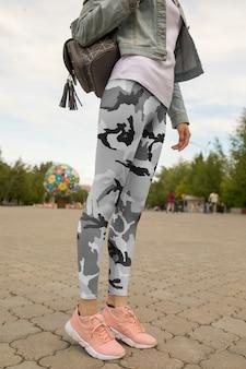 通りでレギンスとバックパックを着ている女性