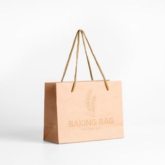 クラフト表面にエンボス加工されたテキストとロゴが入ったショッピングペーパーバッグのモックアップ