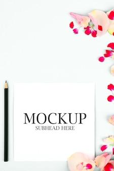 白いノートと美しい花びらのモックアップ