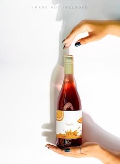 로고 모형과 함께 여성 손에 장미 와인 한 병