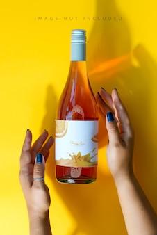 모형과 함께 여성 손에 장미 와인 한 병