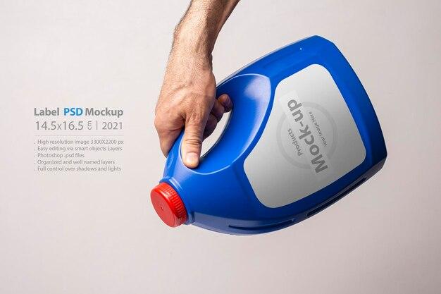 Мужская рука держит синюю бутылку кухонного моющего средства с закрытой крышкой