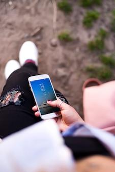 젊은 여자 여행자 앉아서 스마트 폰을 손에 잡고