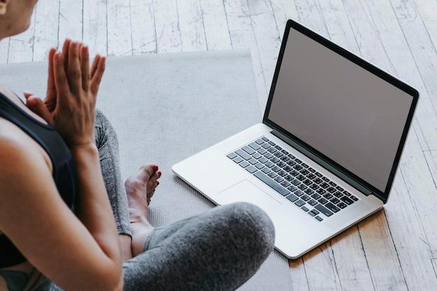 ノートパソコンを介してオンラインでヨガを学ぶアクティブな女性