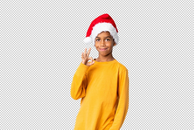African american boy with christmas hat showing ok sign with fingers