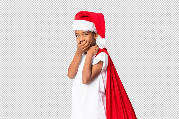 African american boy with christmas hat and taking a bag with gifts doing surprise gesture