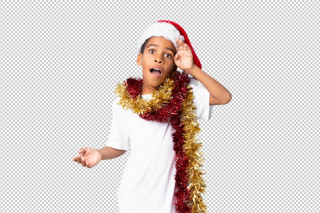 African american boy with christmas hat with surprise and shocked facial expression