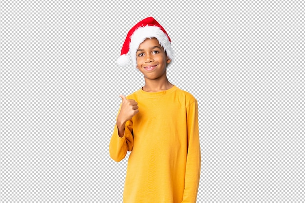 African american boy with christmas hat with thumbs up because something good has happened