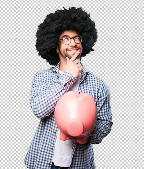 Afro young man holding a piggy bank