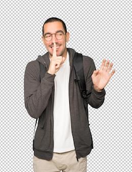 손가락으로 몸짓으로 침묵을 요구하는 놀란 학생
