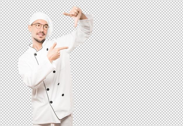 手で写真を撮るジェスチャーを作る驚く若いシェフ