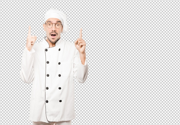 Amazed young chef pointing up with his finger