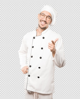 Amazed young chef pointing at you with his finger