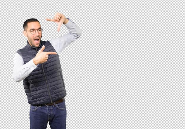 손으로 사진을 찍는 제스처를 만드는 놀란 젊은이