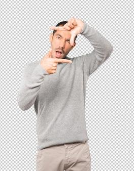 손으로 사진을 찍는 제스처를 만드는 놀란 젊은 남자