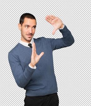 手で写真を撮るジェスチャーをしている驚いた若い男