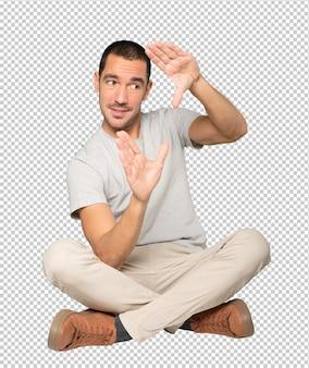 手で写真を撮るジェスチャーをする驚いた若い男