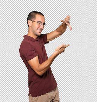 손으로 사진을 찍는 몸짓을 하는 놀란 청년