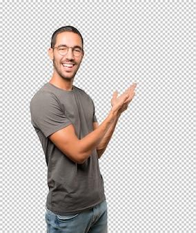 Удивленный молодой человек делает жест приветствия