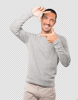 Amazed young man making a gesture of taking a photo with the hands