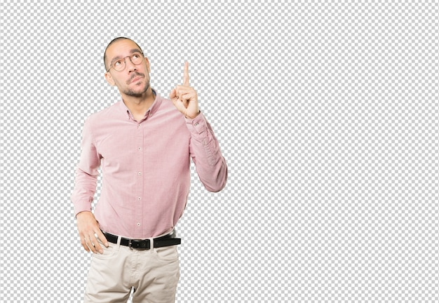 Amazed young man pointing up with his finger
