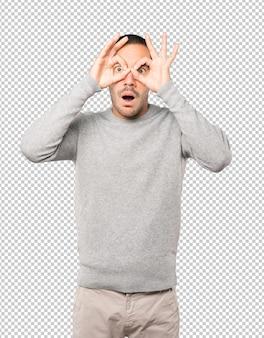 쌍안경처럼 손을 사용하여 놀란 청년