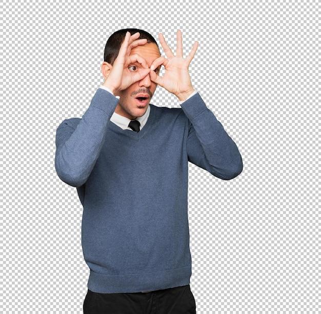 双眼鏡のように手を使って驚いた青年 Premium Psd