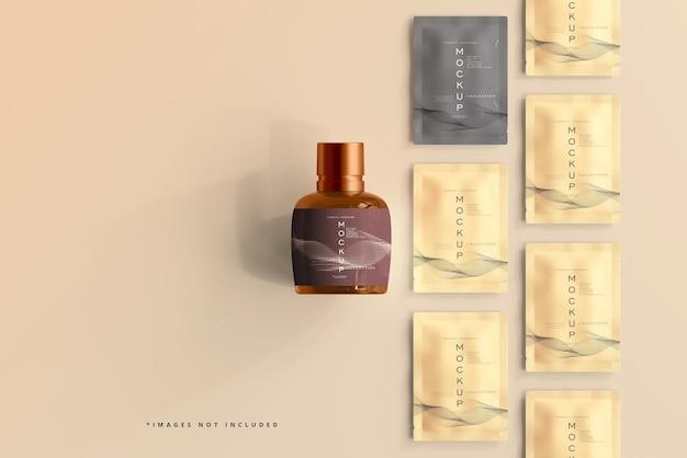 Mockup di bottiglia cosmetica e bustina in vetro ambrato
