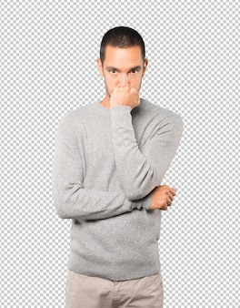 Angry young man posing against background