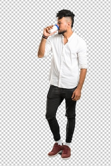 持ち帰り用の紙コップにホットコーヒーを保持している白いシャツとアラビア語の若い男