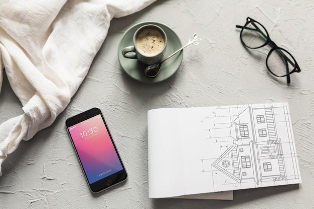 スマートフォンの隣にペーパーモックアップを備えた建築構成
