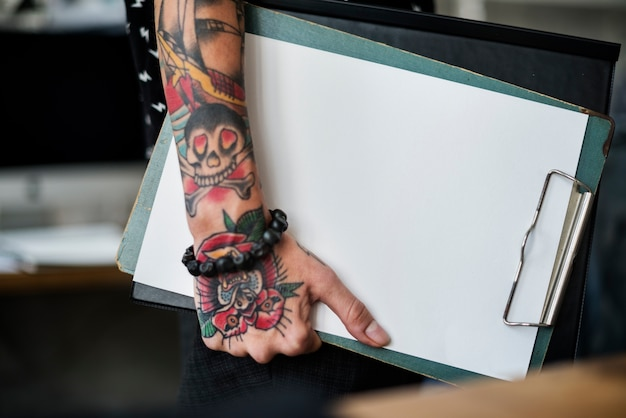 Arm with tattoo carrying clipboard