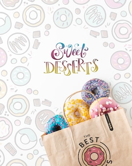 Arrangement of colorful donuts in paper bag with mock-up