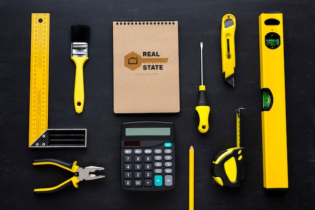 Arrangement of different repairing tools with notepad mock-up on black background