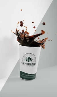 Arrangement of paper coffee cup with coffee splash