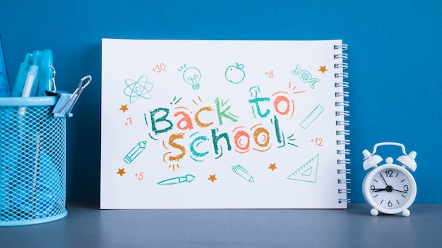 Arrangement with back to school lettering on notebook