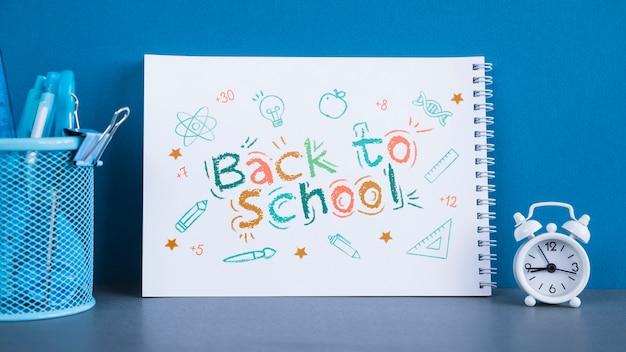 Композиция с надписью обратно в школу на тетради