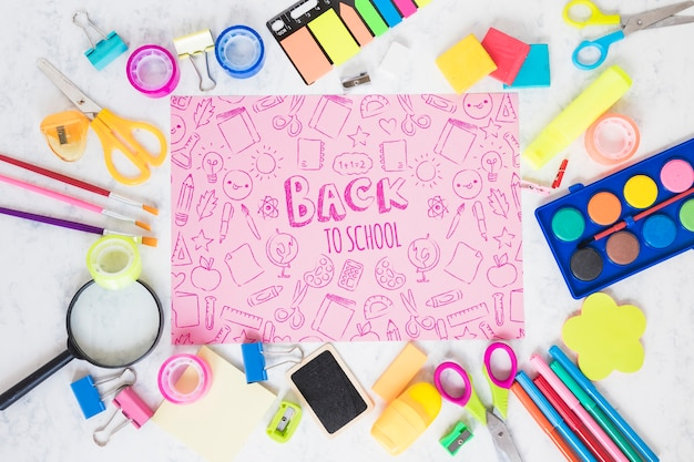 Arrangement with school supplies including magnifying glass