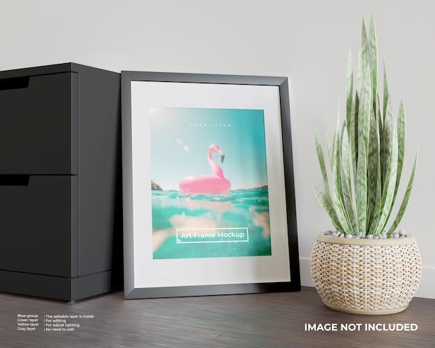Art frame poster mockup leaning against the black cupboard
