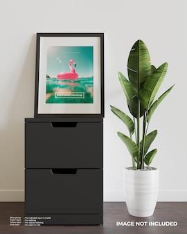 黒い食器棚の上にアートフレームポスターモックアップ