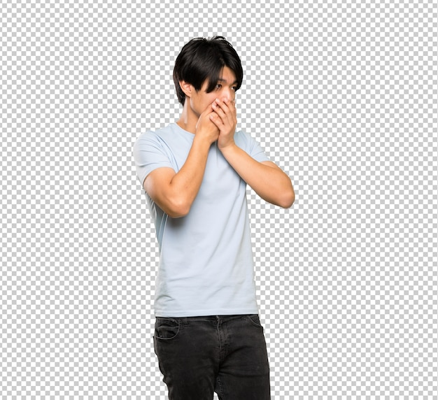 Asian man with blue shirt covering mouth and looking to the side