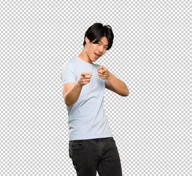 파란색 셔츠 앞을 가리키는 웃 고 아시아 남자