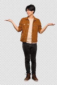 Asian man with brown jacket holding copyspace with two hands