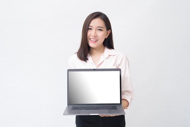 アジアの女性はラップトップのモックアップを保持しています。