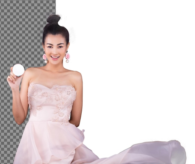 Asian woman wear pink evening gown and fluttering throwing or wind blow skirt in air, isolated. 20s girl smile and present empty cosmetic powder round product, studio white background half body
