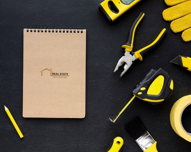 Ассортимент различных инструментов для ремонта с макетом блокнота