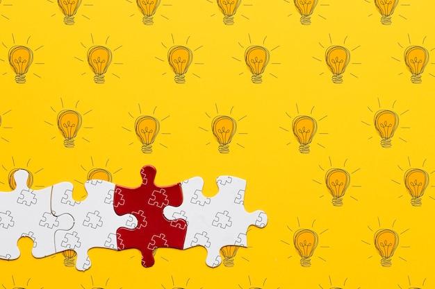 Ассортимент с кусочками головоломки на желтом фоне