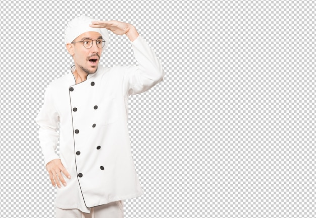 Astonished young chef with a gesture of looking away