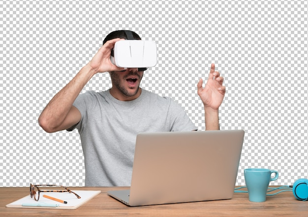 Astonished young man sitting at his desk and using a virtual reality glasses